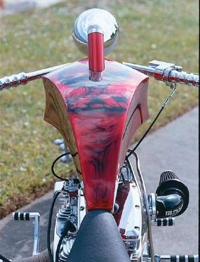 A driver's-eye view of the Suicide Softail reveals a sculpted fuel tank topped by an extended fuel neck with spired cap.