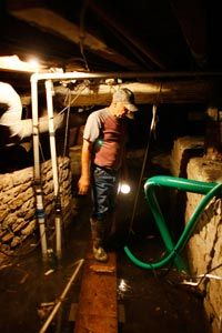 Rex Hipes checks on the sump pump in the basement of the Clarksville Christian church while fighting rising waters from the Mississippi River.