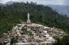 A statue of the Virgin Mary overlooks a village on Luzon Island five months after the eruption of Mount Pinatubo in 1991. Although considerably smaller in scale than a supervolcano, Pinatubo's 1991 eruption lowered temperatures in the Northern Hemisphere.