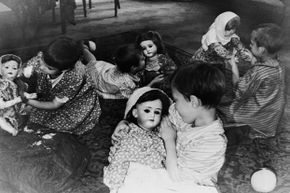 Lifelike dolls hold the interest of four Russian orphans whose parents were killed in the Leningrad siege. When the picture was taken on Jan. 15, 1946, the kids were being cared for in a children's home.