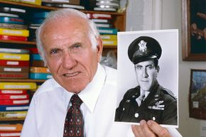 This 1985 picture shows Louis Zamperini holding a photo of himself taken during World War II.