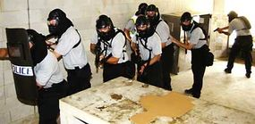 Members of the Arlington Police Department SWAT team trail through a room in Quantico's Combat Town-2.