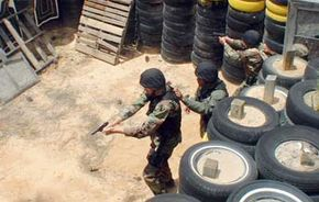 Members of a U.S. Army SWAT team engage targets as they enter a room during two-man team entry drills.
