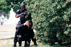 Members of the 60th Security Police Squadron's Base SWAT Team stand behind covering foilage with M-9 pistols ready.
