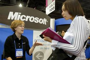 Mikaela Mackin (R) a student at Michigan State University talks to recruiter Jennifer Orchard of Microsoft at the Society of Women Engineers annual conference in Milwaukee, Wisc., 2004.