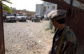 An unidentified Afghan militia Force (AMF) guard watches as U.S. Army Special Forces soldiers prepare to leave their safe house August 31, 2002 in Kunduz, Afghanistan.