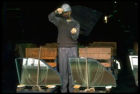 Workers checking safety glass for flaws. See more car safety pictures.