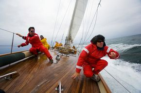 Crew members on a racing yacht brace themselves to stay on the boat. See more pictures of sailing.