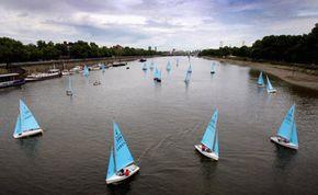 A fleet of 50 Enterprise dinghies sails down the Thames past Chelsea Bridge and Battersea Power Station in London.