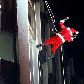 Santa Claus scales a building to deliver presents.