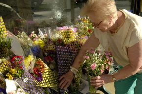 A woman leaves flowers at a memorial for victims of the 2002 D.C. sniper.
