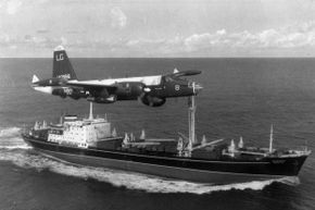 An American P2V Neptune patrol plane flies over a Soviet freighter in 1962.