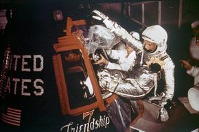 Astronaut John Glenn is loaded into the Friendship 7 capsule in preparation for flight on the Mercury Titan rocket in 1962.