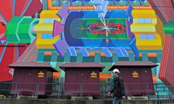 A CERN worker walks past a painted representation of the Large Hadron Collider on Dec. 13, 2011, in Geneva. While the LHC folks didn't discover the elusive Higgs boson in 2011, scientists did report that the search was narrowing.