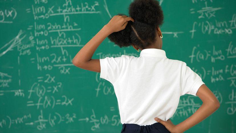 girl scratching head at blackboard