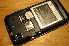 A microSD card can be tricky to handle. Here's one inside a smartphone, carefully tucked under a small metal bracket next to the microSD logo.