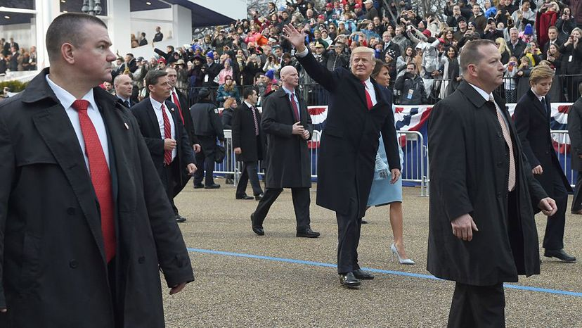 U.S. President Donald Trump walks his wife Melania, surrounded by Secret Service officers outside the White House, as the presidential inaugural parade winds through Washington, D.C. TIMOTHY A. CLARY/AFP/Getty Images