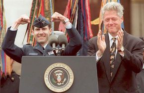 U.S. President Bill Clinton applauds as U.S. Air Force pilot Captain Scott O'Grady raises his fists during ceremonies at the Pentagon to welcome O'Grady home.