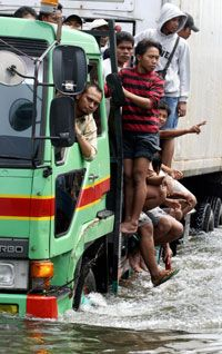 Jakarta, Indonesia residents ride a truck through a flooded street after an unusual high tide in November 2007.