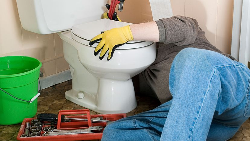 man repairing toilet