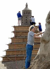 German sculptors work on a sand replica of the pharos during a sand sculpting competition in