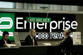 Enterprise Rent-A-Car counter employees help a customer at Lambert International Airport in St. Louis.