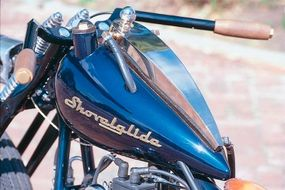 Perched atop the fuel tank with its Shovelglide logo is the hand-formed oil tank -- tinted gold to match other trim on the bike. The wood handgrips match the wood floorboards, yet another example of this chopper's meticulous detailing.