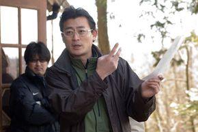 """Director Masayuki Ochiai maps out a scene on the set of """"Shutter."""""""