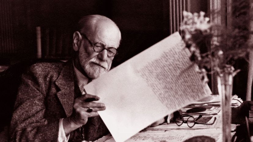 Sigmund Freud, the father of psychoanalysis, works at his desk. World History Archive/UIG via Getty images