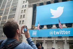 A Twitter banner (including the famous @ sign) is displayed in front of the New York Stock Exchange during Twitter's initial public offering in 2013.