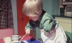 A Thalidomide child painting at home.
