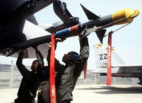 Securing a Sidewinder to the missile launcher on an F-15 Eagle