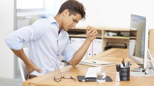 Why is sitting in a chair for long periods bad for your back?