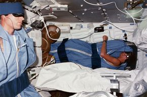 Pilot Michael L. Coats (left) and mission specialist Steven A. Hawley (right) fall asleep listening to music on the lower deck of the shuttle Discovery. What's it like for an astronaut to sleep in space? See more astronaut pictures.