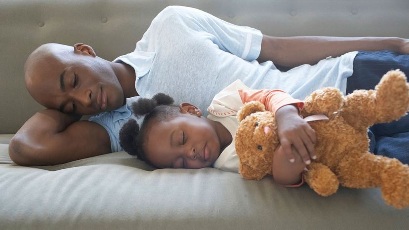man, daughter and teddy sleeping on side
