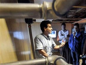 Dean Kamen, left, sits on an energy-efficient Stirling engine that he used in Bangladesh to create electricity with methane gas generated by cow dung.
