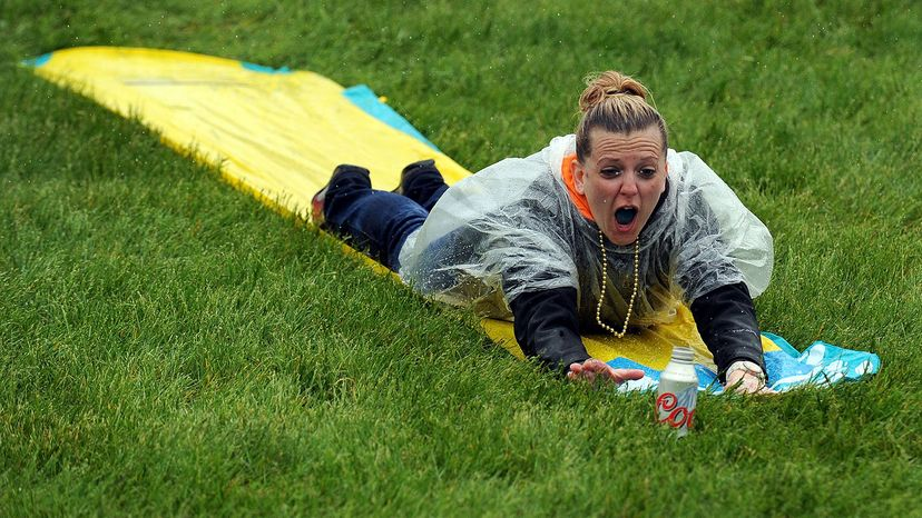 adult sliding down Slip 'N Slide