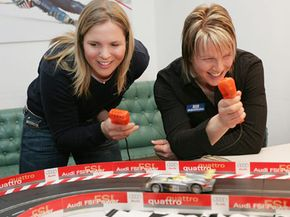 Top skiers Anja Paerson of Sweden, left, and Germany's Hilde Gerg relax while racing each other on a Carrera slot car course at the Audi lounge in Bormio, northern Italy, Feb. 1, 2005.