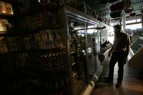 A grocer contemplates a refrigerator full of food during a three-week, 2006 blackout in New York City. According to the DOE, five major blackouts have occurred in the past 40 years. Three of which occurred in the past nine years.
