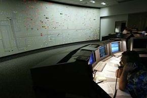 A transmission dispatcher helps manage the flow of electricity during a 2004 heat wave in California. Note the map tracking the flow of electricity through the entire state.