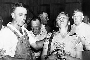 1945: Lewis Ford is shown as he draped a rattlesnake about the neck of a member of a Tennessee congregation. Ford would die that same year from a snake bite he received.