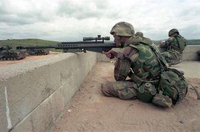 A U.S. Marine Sniper sights a target through a scope on a 12.7 mm .50-caliber light Fifty Model 82A1 Sniper Rifle.