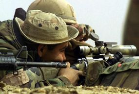 A sniper sights in a target on a range.