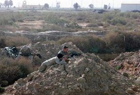 A sniper team stalks in an open field in Iraq.