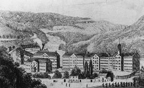 Tenement buildings in the folds of wooded hills at New Lanark.