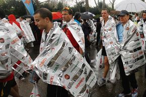 Image Gallery: Olympics Competitors in the Flora London Marathon keep warm with space blankets. See pictures of the Olympics.