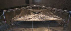 A four-quadrant solar sail system created by NASA's solar sail propulsion team at the Marshall Space Flight Center in Huntsville, Ala., and its industry partner, L'Garde, Inc. sits fully deployed in a 100-foot-diameter vacuum chamber at NASA's Glenn Research Center.
