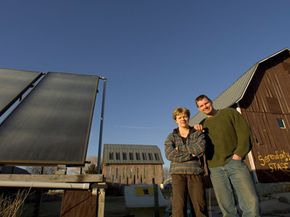 Lisa Kivirist and John Ivanko stand next to a solar thermal system that heats a greenhouse at their bed-and-breakfast.
