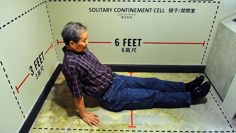 Harry Wu sits in an exhibit showing the exact dimensions of his solitary confinement cell  in China, on display at Laogai Museum in Washington, D.C. Wu, who was a human rights activist, spent 19 years in labor prison camps in China. Ricky Carioti/The Washington Post via Getty Images