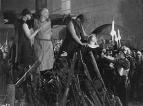 """Circa 1933: British actor Matheson Lang is chained to a cross during the Spanish Inquisition in a scene from the film """"The Wandering Jew."""""""